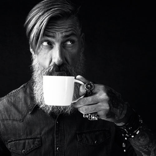 Man Looking Upwards To the Right While Drinking Coffee